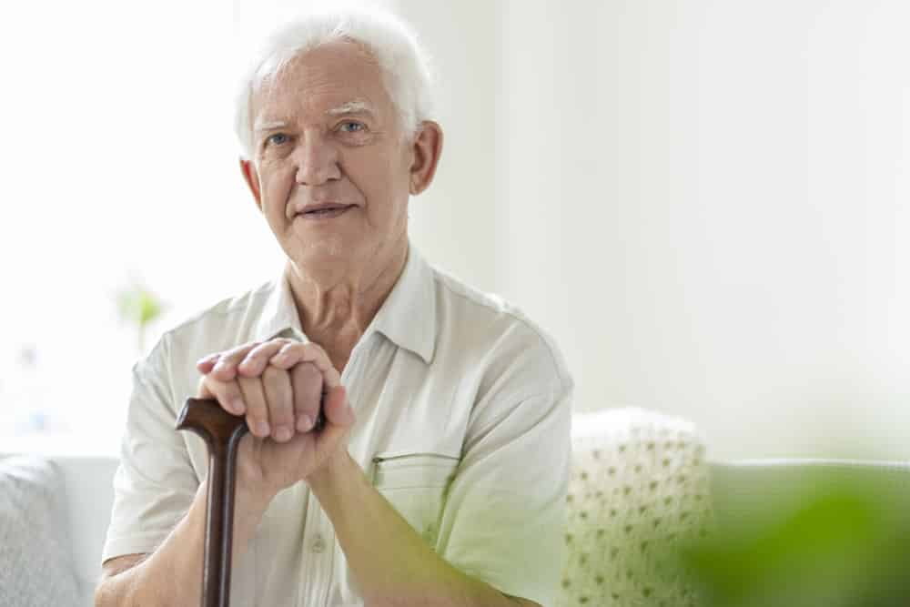 Senior man sitting, holding a walking stick
