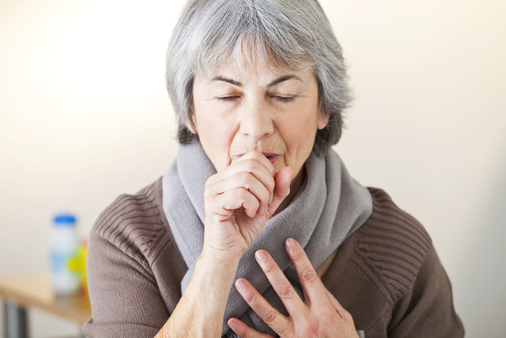 Senior woman coughing into hand